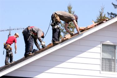 Roof Installation in Gridiron TX. Three roofers laying new shingle on a roof in Gridiron.
